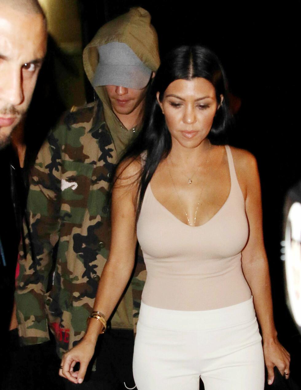 SEXY: Kourtney var flott i tettsittende hvite bukser og en hudfarget utringet topp. Bieber skjulte seg bak en caps og militærjakke. Foto: Splash News