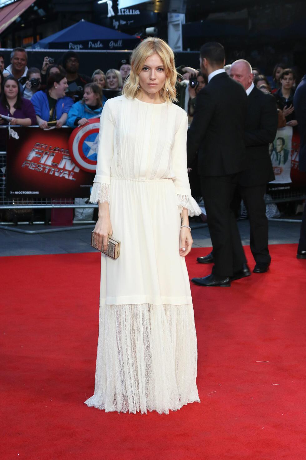BOHEMSK: Sienna Miller i en florlett, hvit kjole fra Michael Kors´kommende vårkolleksjon på «High-Rise»-visningen. Hun stylet kjolen med diskret sminke og en glitrende boksclutch.  Foto: Splash News