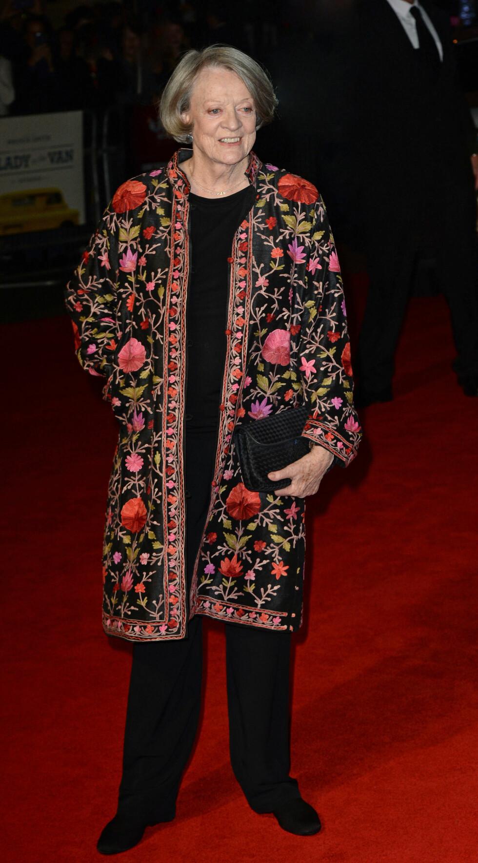 FARGEKLATT: «Downton Abbey»-stjernen Maggie Smith livet opp sitt helsorte antrekk med en brodert kåpe på «The Lady in the Van»-visningen den 13. oktober.  Foto: Splash News
