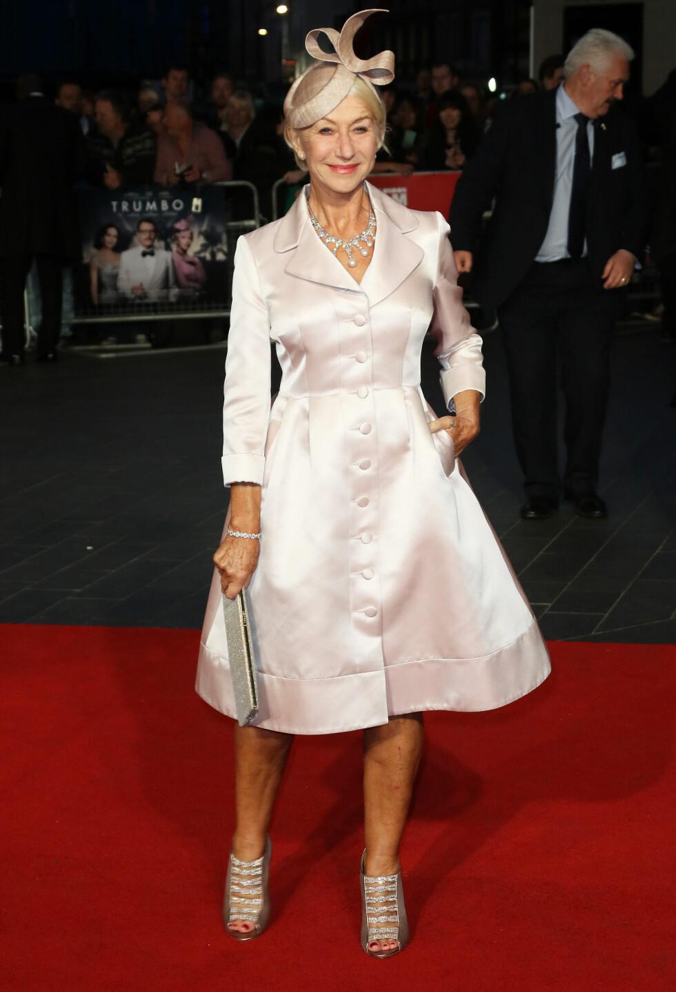 SATENG: Helen Mirren i en A-formet, blekrosa kåpekjole på «Trumbo»-visningen. Skuespilleren tok den helt ut med matchende sko, glitrende tilbehør og en festlig hatt.  Foto: Splash News