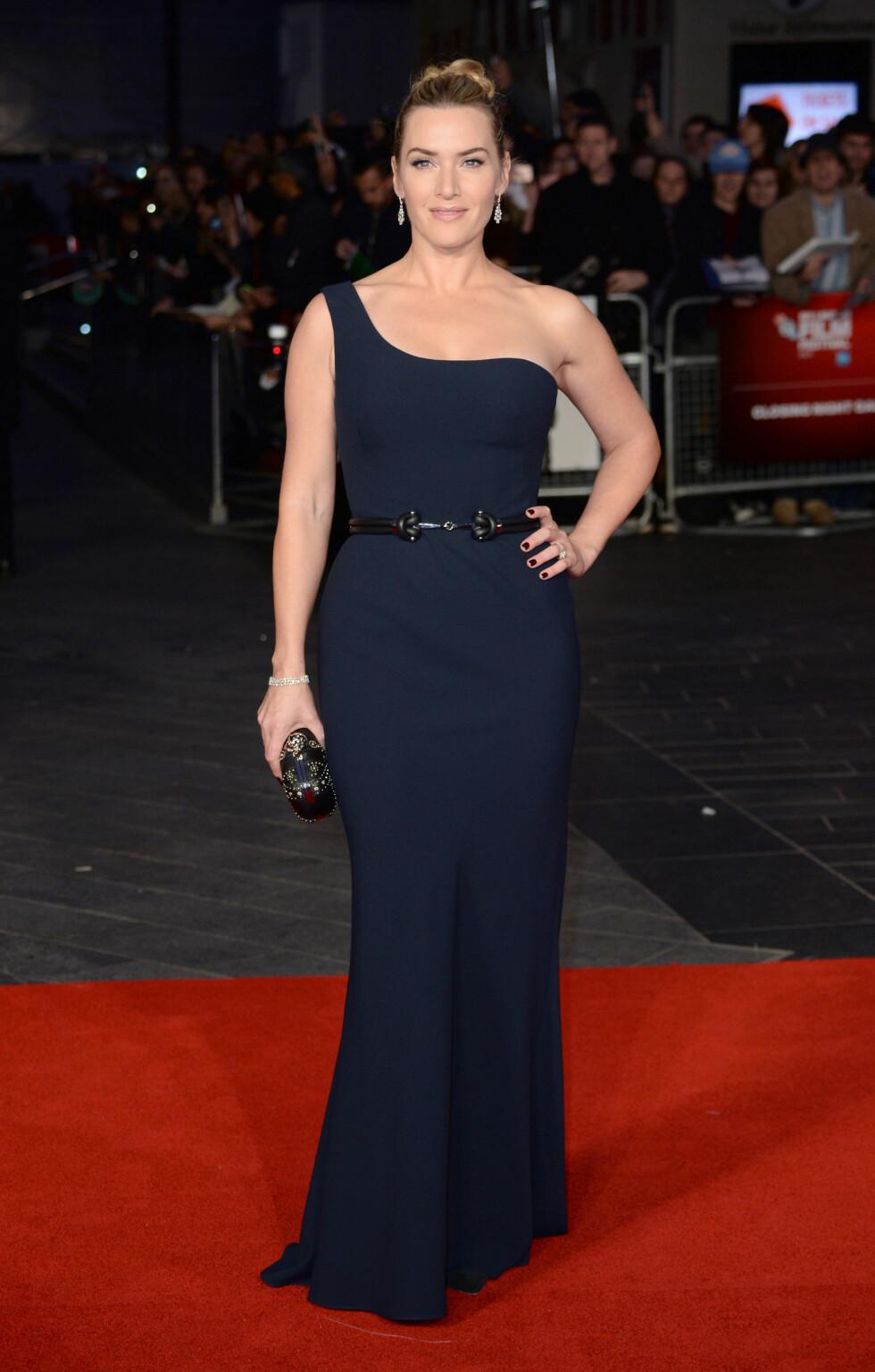 SENSUELL: Kate Winslets former kom virkelig til sin rett i denne marineblå Alexander McQueen-kjolen på «Steve Jobs»-premieren. Hun stylet kjolen med boksclutch fra samme merke og smykker fra Boucheron og De Beers. Foto: Pa Photos