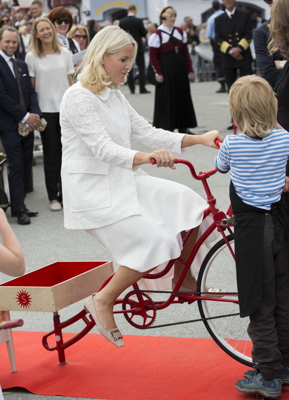 SPORTY PRINSESSE: Kronprinsesse Mette-Marit tråkket til på «smoothie-sykkelen» i Ravnkloa i Trondheim torsdag formiddag, selv om hun var iført finstasen. Foto: Danapress