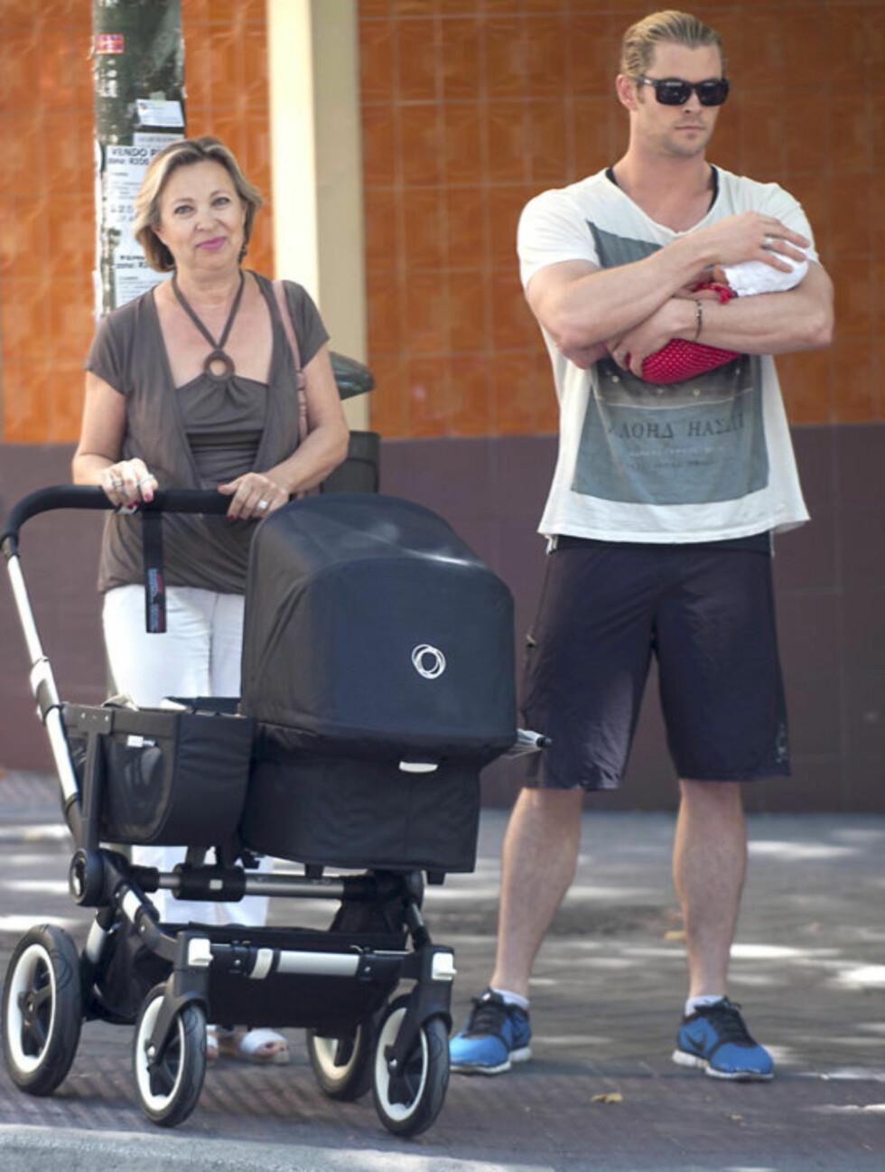FAMILIETUR: Også Chris Hemsworths svigermor, Cristina Medianu, var med på spaserturen. Hun måtte tilsynelatende nøye seg med å trille tom vogn mens filmstjernen holdt godt på datteren sin.  Foto: © GTRESONLINE