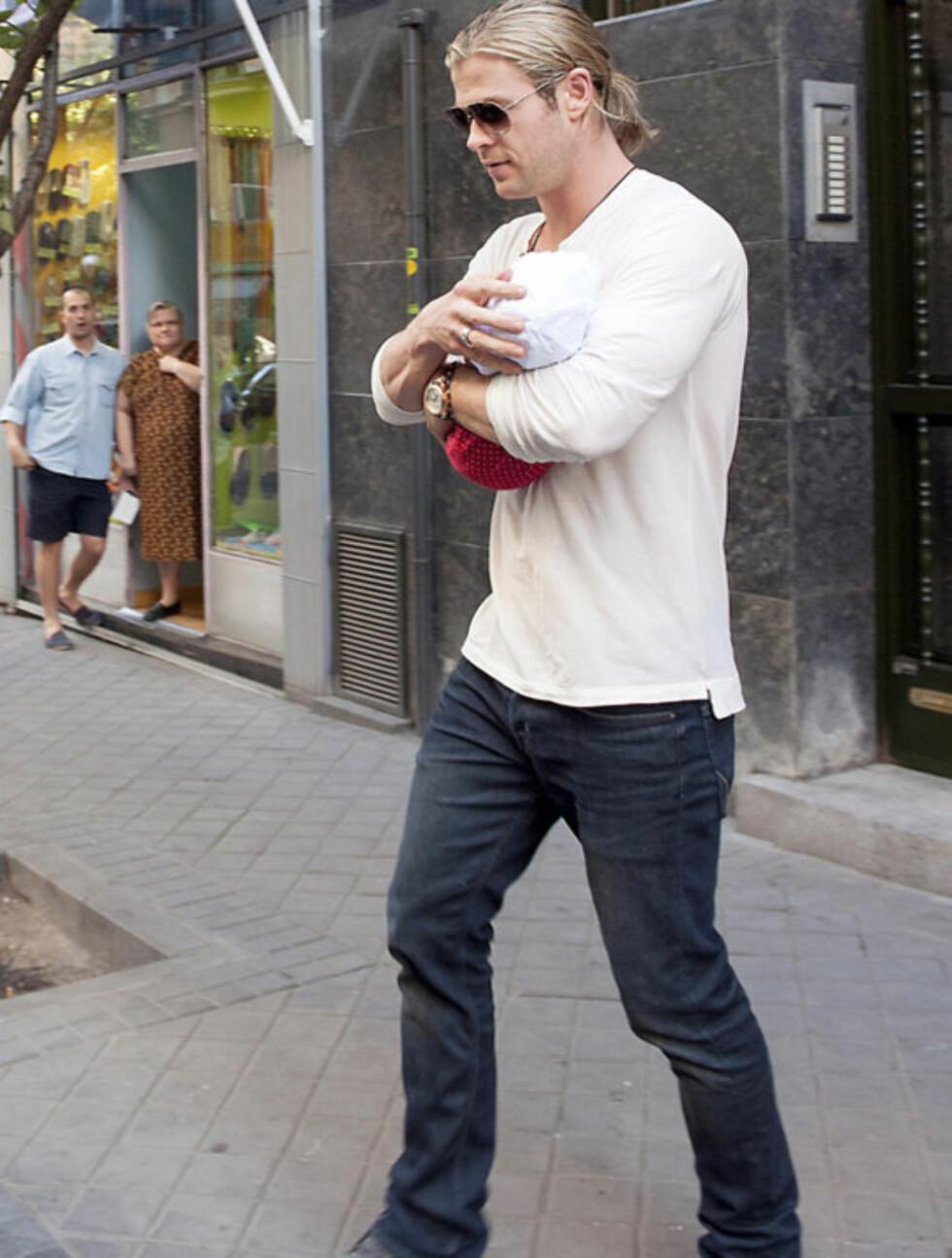 GODT GREP: Chris Hemsworth passet godt på datteren ute på gaten i Madrid mandag. Kjekkas-pappaen vakte tydeligvis interesse i byen.  Foto: Stella Pictures