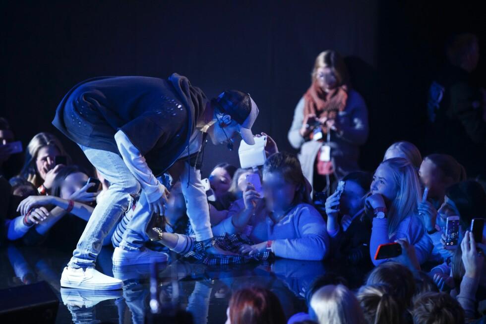VANNSØL PÅ SCENEN: Her tørker Justin Bieber opp vann på scenegulvet med en skjorte. Anne står til høyre blant publikum og tar bilde av opptrinnet. Foto: NTB scanpix