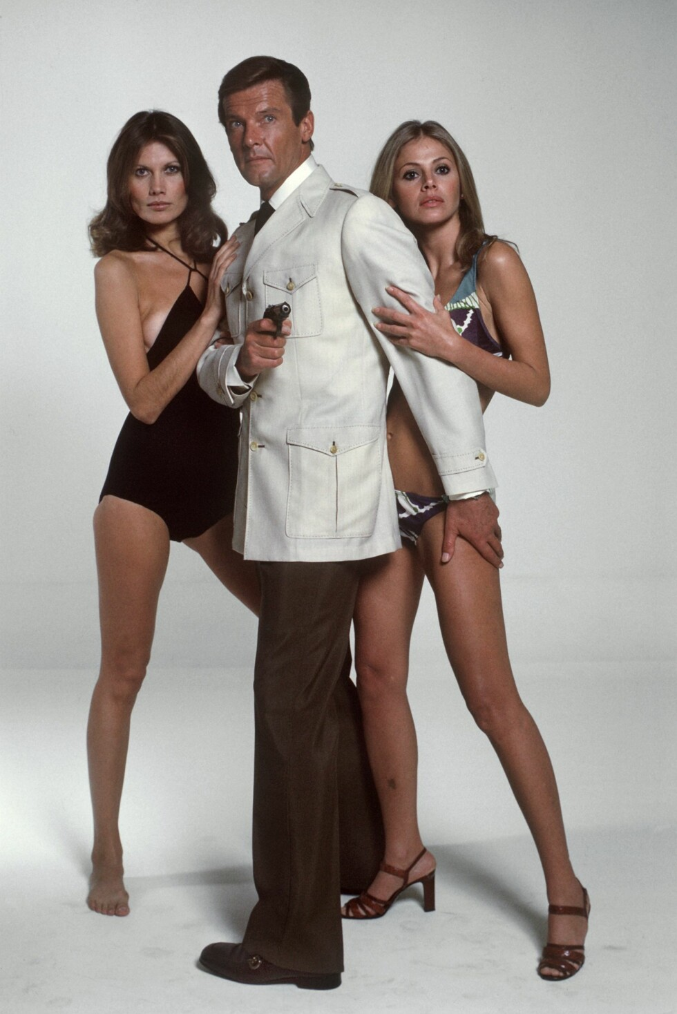 PÅ LERRETET: Fra 1973 til 1985 spilte Roger Moore i syv James Bond-filmer. Her med Maud Adams og Britt Ekland i «The Man with the Golden Gun» fra 1974. Foto: DPA