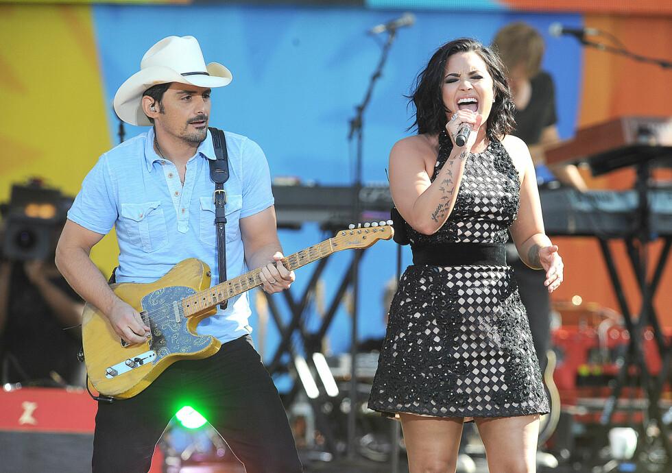PÅ SCENEN: Gjennom musikken har Lovato nådd ut til mange med sin vonde historie. Her synger hun med Brad Paisley i Central Park i New York i helgen. Foto: Broadimage