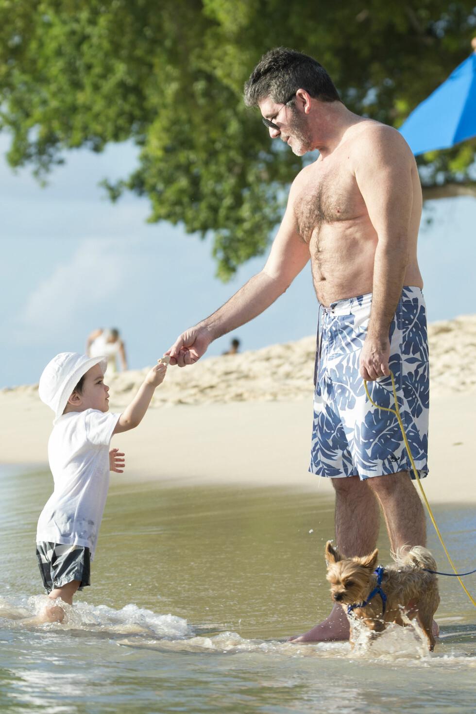 ELSKER FARSROLLEN: Simon Cowell er tydelig på at rollen som pappa for lille Eric har forandret og beriket livet hans. Her er far og sønn sammen med en av familiens hunder på Barbados før jul. Foto: Xposure
