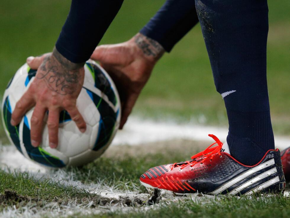 SYMBOLSK: David Beckham har tatovert «Love» på venstre hånd, og har også fått navnene på de fire barna gravert på fotballskoene. Foto: All Over Press
