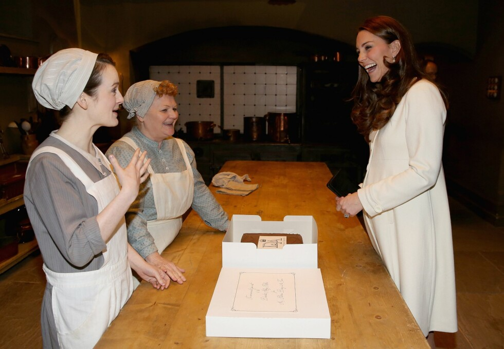 LATTERMILDT: Hertuginne Kate i samtale med skuespillerne Sophie McShera (Daisy Mason) og Lesley Nicol (Mrs. Patmore) på «Downton Abbey»-settet i Ealing Studios i Vest-London våren 2015. Den gang var hertuginnen gravid med lille prinsesse Charlotte. Foto: Afp