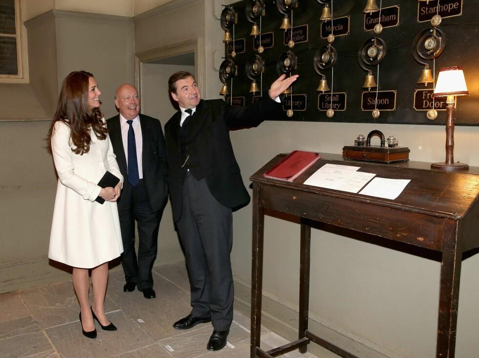 STOR STAS: Hertuginne Kate blir vist de berømte bjellene tjenerstaben må forholde seg til i «Downton Abbey». Serieskaper Julian Fellowes står i midten, og skuespiller Brendan Coyle (butleren John Bates) står til høyre.  Foto: Afp
