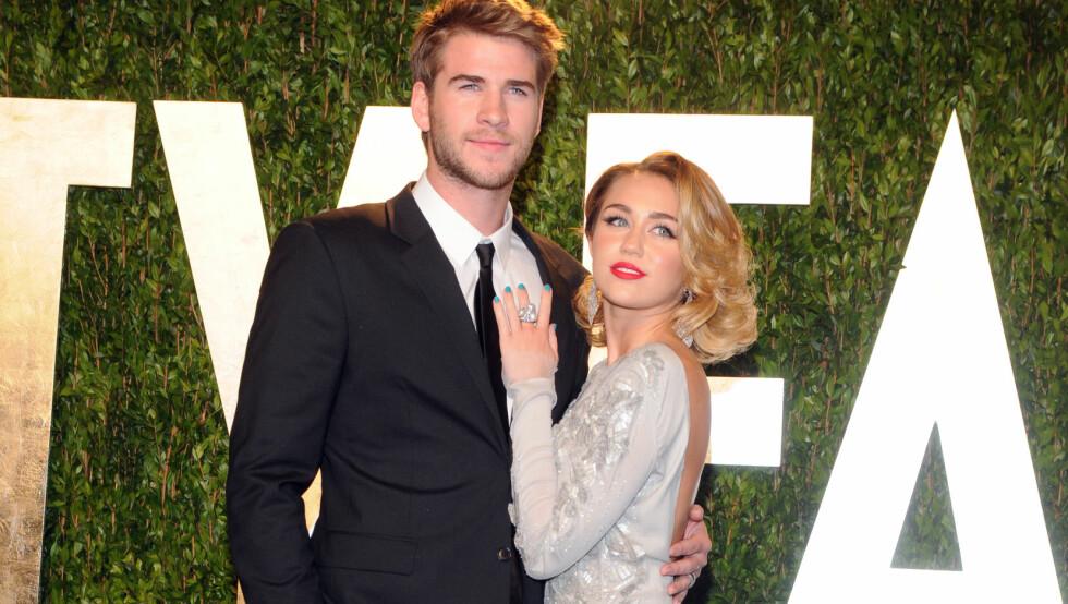 RINGER KIRKEKLOKKENE?: Life & STyle hevder at det tidligere stjerneparet Liam Hemsworth og Miley Cyrus har forlovet seg for annen gang. Etter bruddet i 2013 uttalte Miley at hun den gang var for ung til å forstå hva en forlovelse innebar. Her er de to sammen på Vanity Fairs Oscar-fest i 2012.  Foto: NTB Scanpix