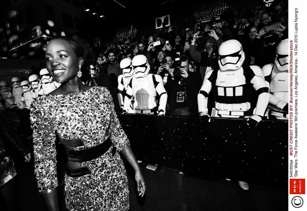 STORMTROOPERS: Oscar-vinner Lupita Nyong´o glitrer foran statister utkledd som Stormtroopers på «Star Wars: The Force Awakens»-premieren.  Foto: Rex Features