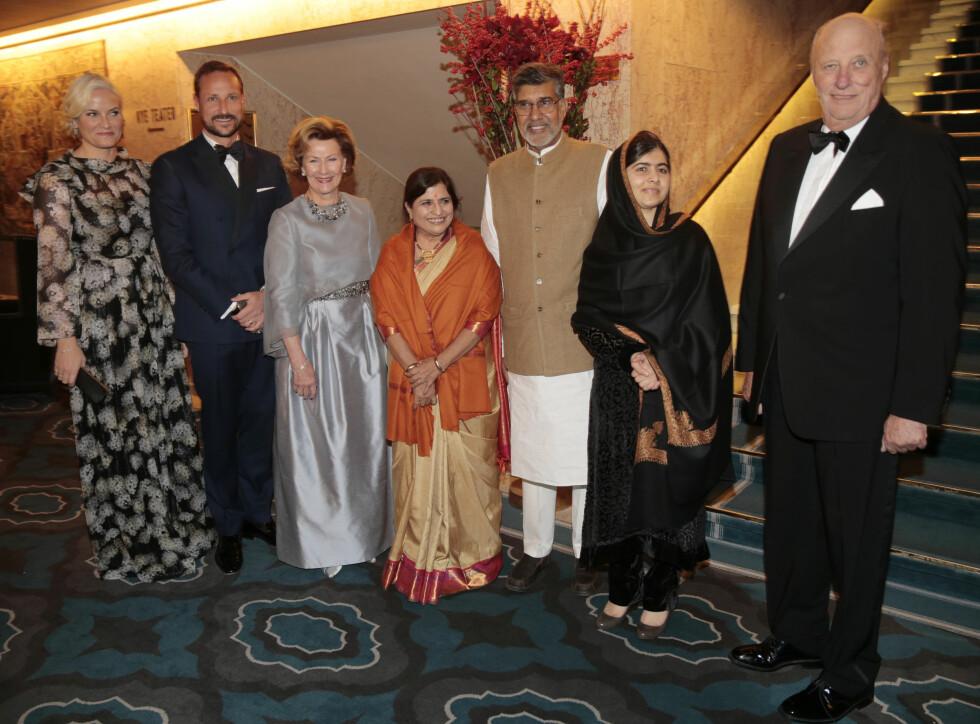 BLOMSTERDRØM: I fjor fikk Mette Marit mye skryt for sin gulvlange blomsterkjole med med lange ermer, gjennomsiktige partier og metalliske detaljer. Hennes blonde lokker var også vakkert satt opp. Her sammen med fjorårets Nobel-vinnere Malala Yousafzai og Kailash Satyarthi, samt hans kone Sumedha. Foto: NTB scanpix