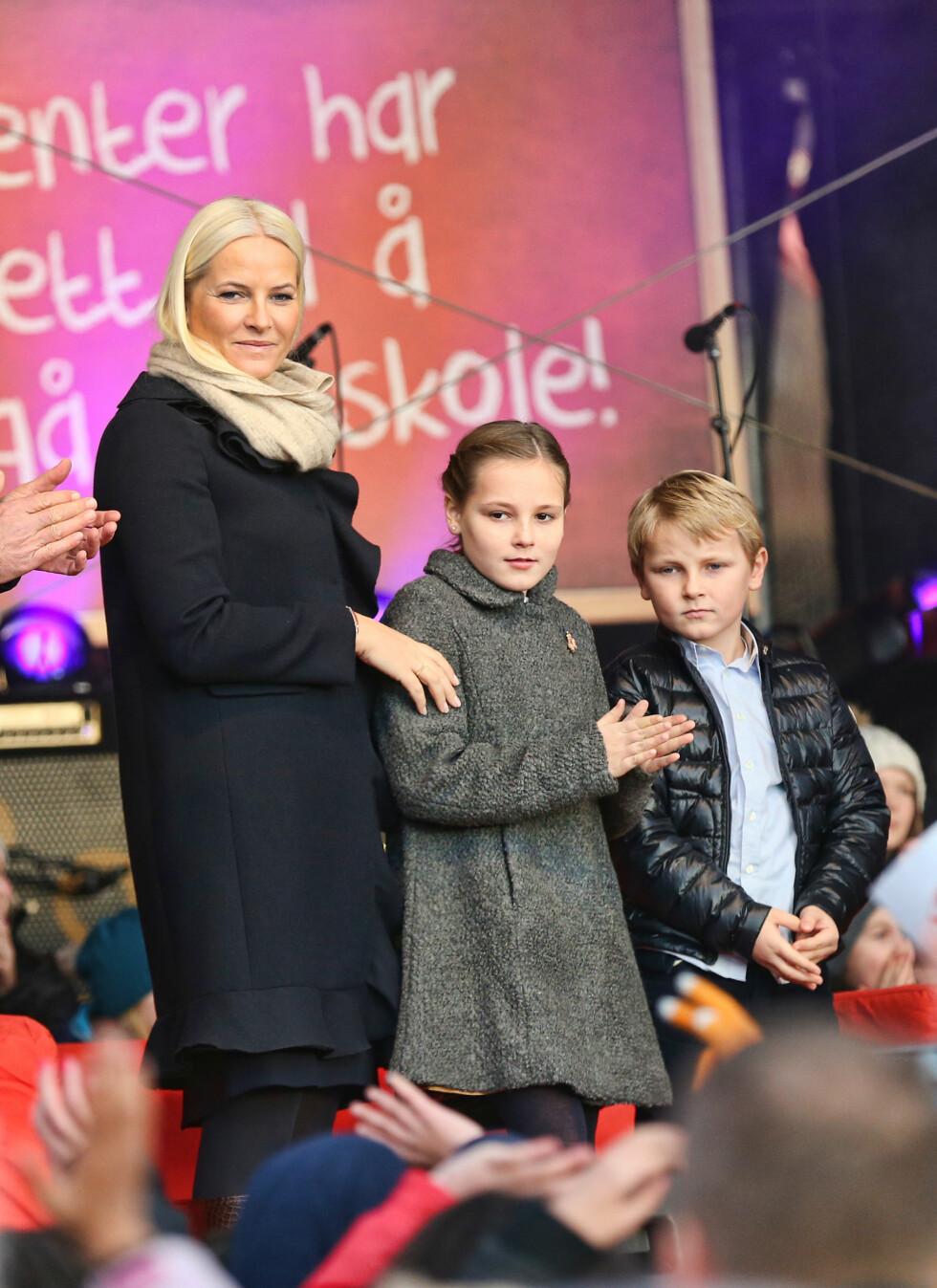 HYLLET MALALA: Mette-Marit, Sverre Magnus og Ingrid Alexandra kastet glans da Malala sto på utendørsscenen på Redd Barna-arrangementet i fjor. Foto: Andreas Fadum
