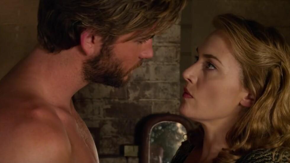 FILMFLØRT: I dramafilmen «The Dressmaker» faller rollefigurene til Liam Hemsworth og Kate Winslet for hverandre. Den 15 år gamle datteren til Winslet skal ha blitt sjalu på morens tette samarbeid med «Hunger Games»-kjekkasen. Foto: Skjermdump fra YouTube