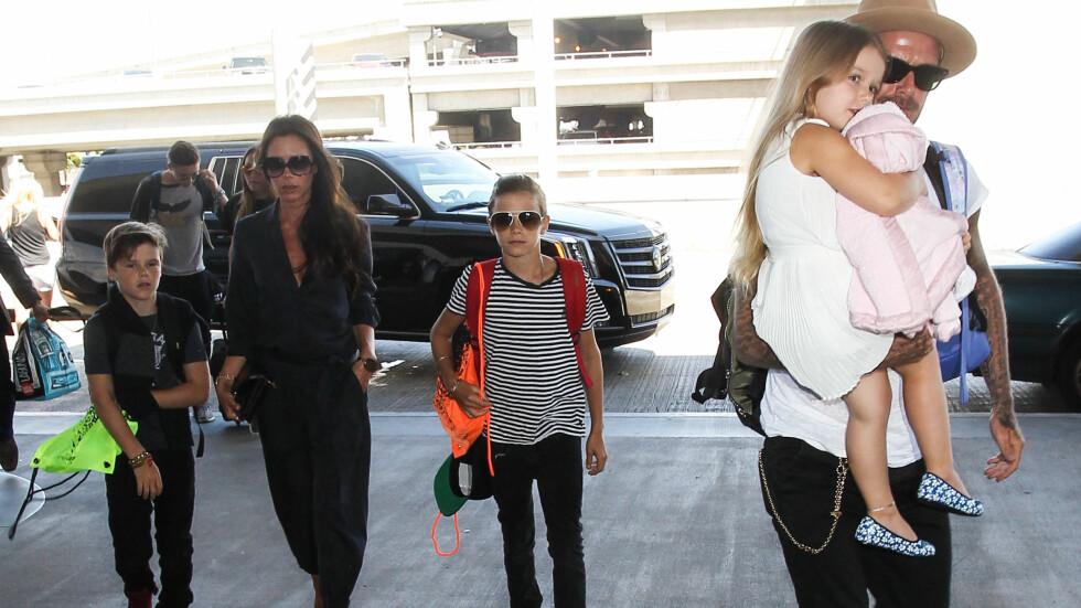 ELSKER FAMILIELIVET: David Beckham har virkelig begynt å bruke sin veltrente kropp som et lerret for familien sin. Her er han på flyplassen i Los Angeles i august sammen med datteren Harper, kona Victoria og sønnene Brooklyn (bak t.v.), Cruz og Romeo (midten).  Foto: Splash News