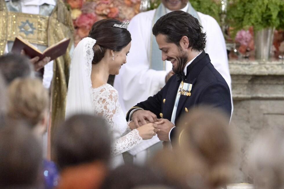 RING PÅ FINGEREN: Prins Carl Philip slet litt med å få ringen på brudens finger - men det tok de begge med godt humør. Foto: NTB scanpix