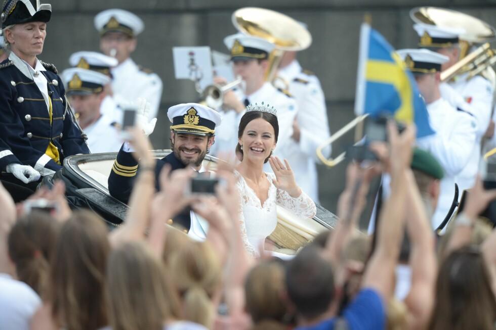 HYLLET AV FOLKET: Prinsesse Sofia og prins Carl Philip ble kjørt rundt i Stockholms gater for å motta hyllest etter bryllupet. Foto: NTB Scanpix