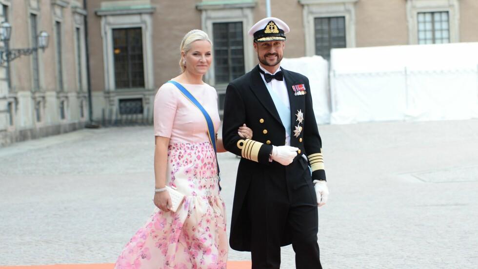 ROSA PÅ BALL: Kronprinsesse Mette-Marit var kledd i blomsterdekorert skjørt fra Temperley London og en spesialdesignet overdel fra Nina Skarra da hun ankom det svenske bryllupet i følge med sin uniformskledde ektemann Haakon.  Foto: NTBscanpix