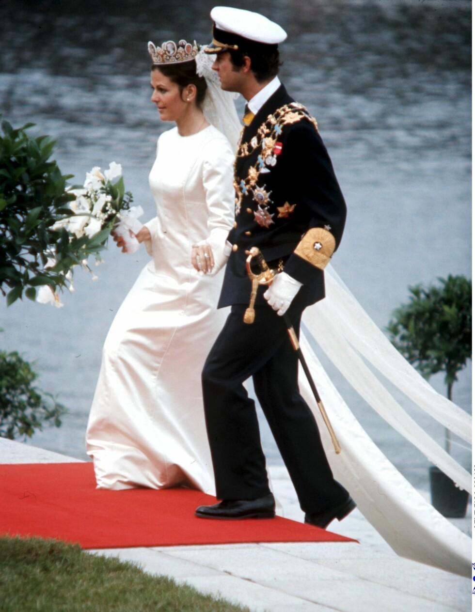 HÅND I HÅND: Dronning Silvia strålte i sin enkle brudekjole fra Christian Dior, mens kong Carl Gustaf var staut i uniform.  Foto: Scanpix Sweden