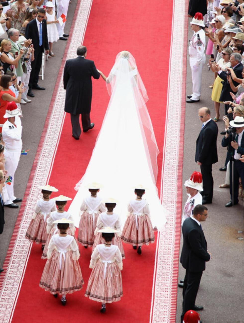 <strong>LANGT SLEP:</strong> Slepet på Charlenes brudekjole fra Giorgio Armani var drøye 20 meter langt og bød på litt hodebry... Her blir hun ledet til alters av sin far lørdag 2. juli i Monte Carlo, Monaco.  Foto: All Over Press
