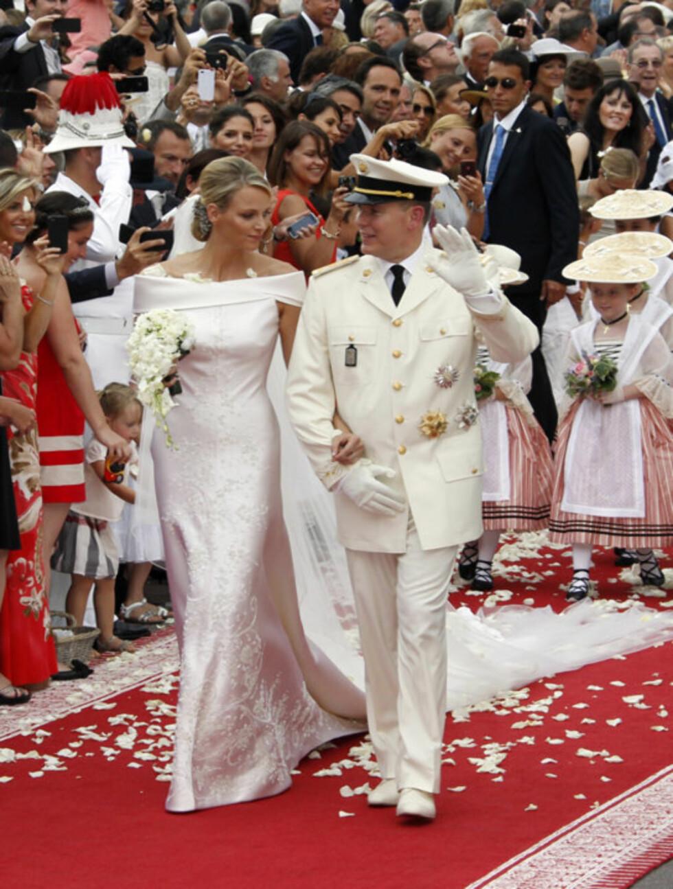 <strong>HYLLET:</strong> De nygifte ble hyllet med et regn av hvite roseblader da de forlot den kongelige borggården etter vielsen lørdag.  Foto: Scanpix