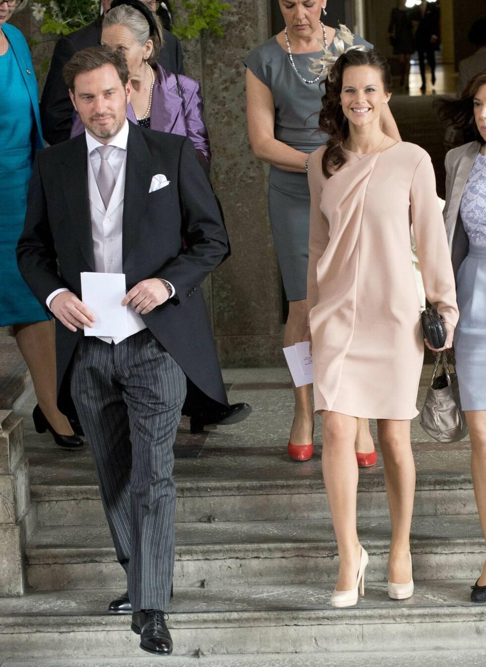 VÅREN 2012: Sofia, her sammen med Chris ONeill, iført en delikat, pudderfarget kjole i anledning prinsesse Estelles dåp. Den sorte clutchvesken og hodepryden gjør antrekket mer spennende. Legg merke til de beige pumpsene, som er av samme type som hertuginne Kates favorittsko. Foto: Afp