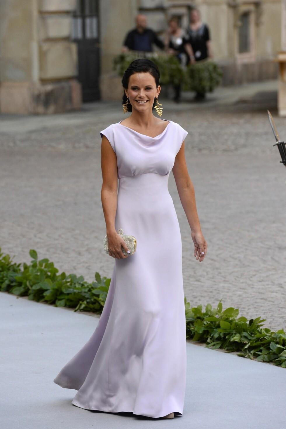 SOMMEREN 2013: Sofia Hellqvist ankommer prinsesse Madeleine og Chris ONeills bryllup. Den yndige kjolen får mer personlighet av de store øredobbene og den glitrende clutchvesken. Foto: Afp