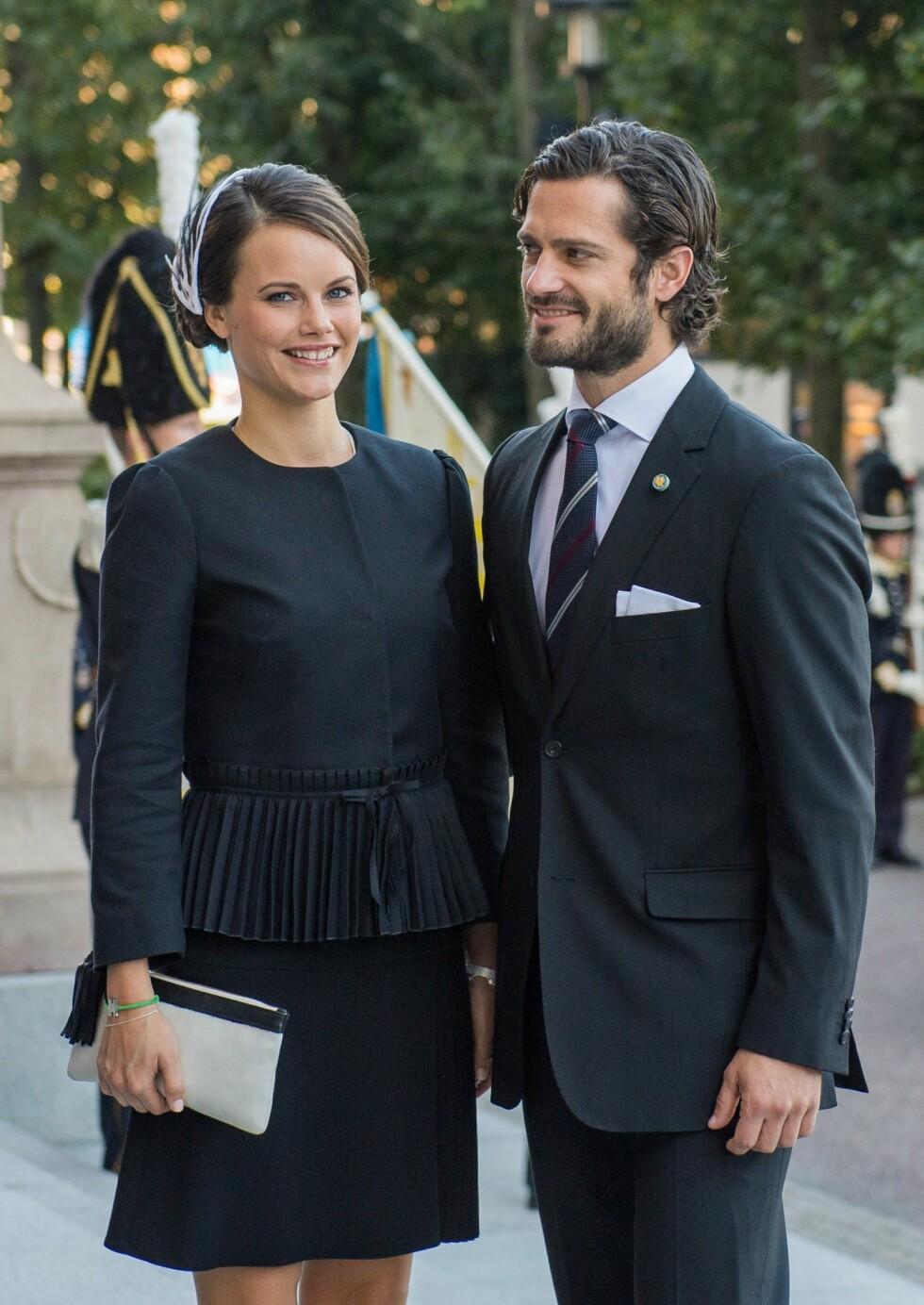 HØSTEN 2014: Prins Carl Philip og Sofia Hellqvist ankommer åpningen av det svenske parlamentet i Stockholm. Legg merke til den sorte og hvite fjærpynten og de sorte frynsense på vesken hennes - som matcher jakken.  Foto: Afp