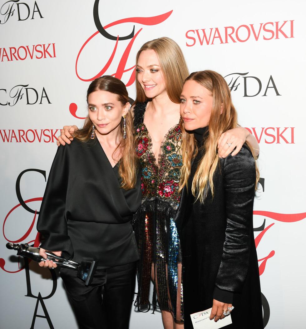 PRISVINNERE: Ashley og Mary-Kate Olsen poserer sammen med skuespiller Amanda Seyfried, etter å ha mottatt den gjeve prisen for årets kvinnelige klesdesign. Foto: SipaUSA