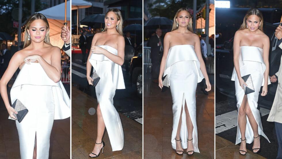 KRANGLETE KJOLE: Chrissy Teigen var flott i hvitt da hun ankom CFDA Fashion Awards mandag kveld, men både kjolens splitt og skjæring over brystet bød på problemer for stjernen. Foto: NTB Scanpix