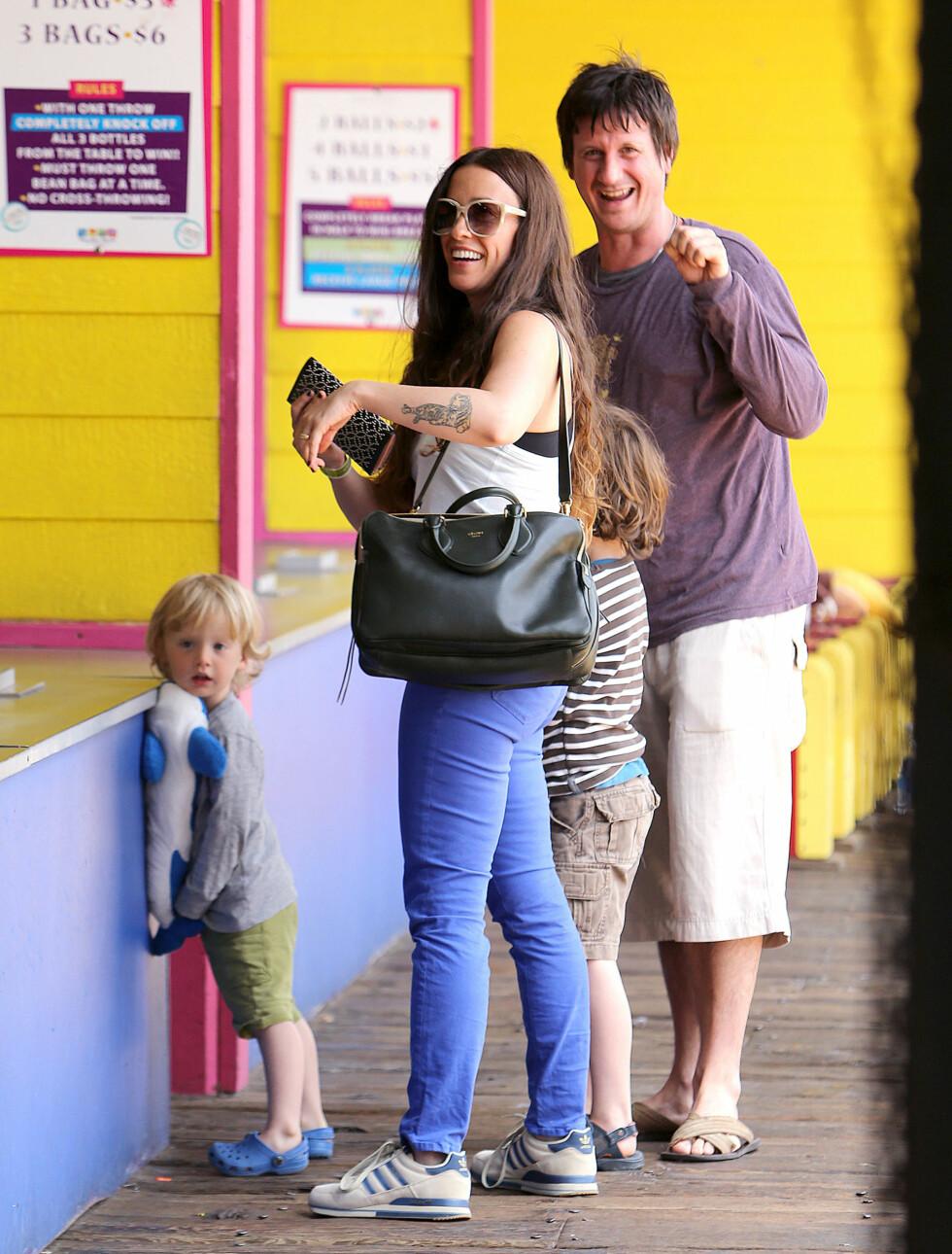BEGGE ER MUSIKERE: Alanis Morissette og tvillingbroren Wade koser seg sammen på Santa Monica Pier i Los Angeles sammen med Wades sønn. Foto: All Over Press
