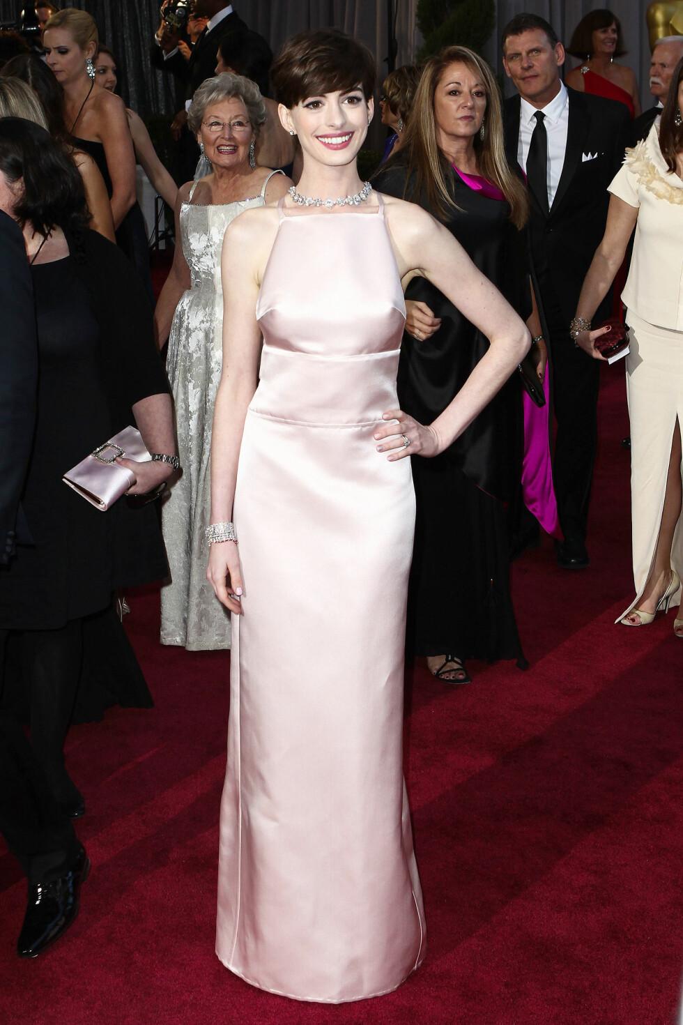 I 2013: Anne Hathaway valgte i siste liten bort Valentino-kjolen sin, ettersom den lignet for mye på kjolen til en av de andre Oscar-stjernene. Dermed endte hun opp med denne blekrosa kreasjonen fra Prada, som gjorde henne svært få tjenester.  Foto: Splash News/ All Over Press