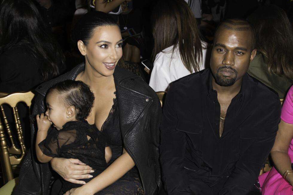 KJENDISBABY: Kim Kardashian og Kanye West tar gjerne med datteren på celebre arrangementer og kler henne opp i antrekk som matcher dem. Her på Givenchy-visningen under moteuken i Paris høsten 2014.  Foto: Corbis/All Over Press