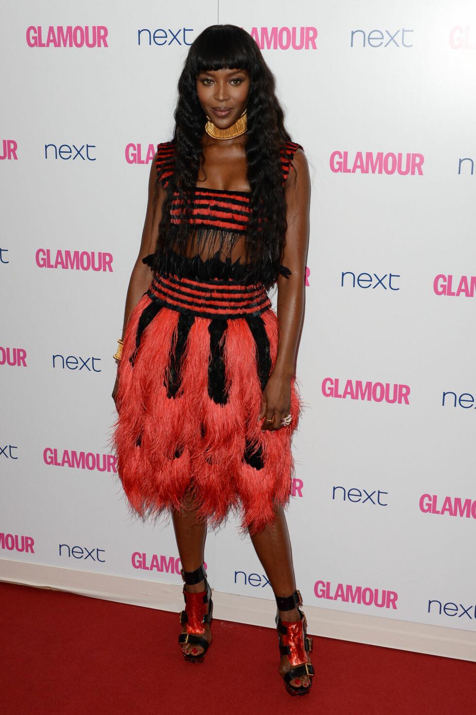 FJÆR: Naomi Campbells spesielle fjærkjole i rødt og sort, kombinert med voldsomme sko og smykker på Glamour Awards i juni, ble nok for mye for Seoghør.nos lesere - som trillet terningen til én. Foto: Stella Pictures
