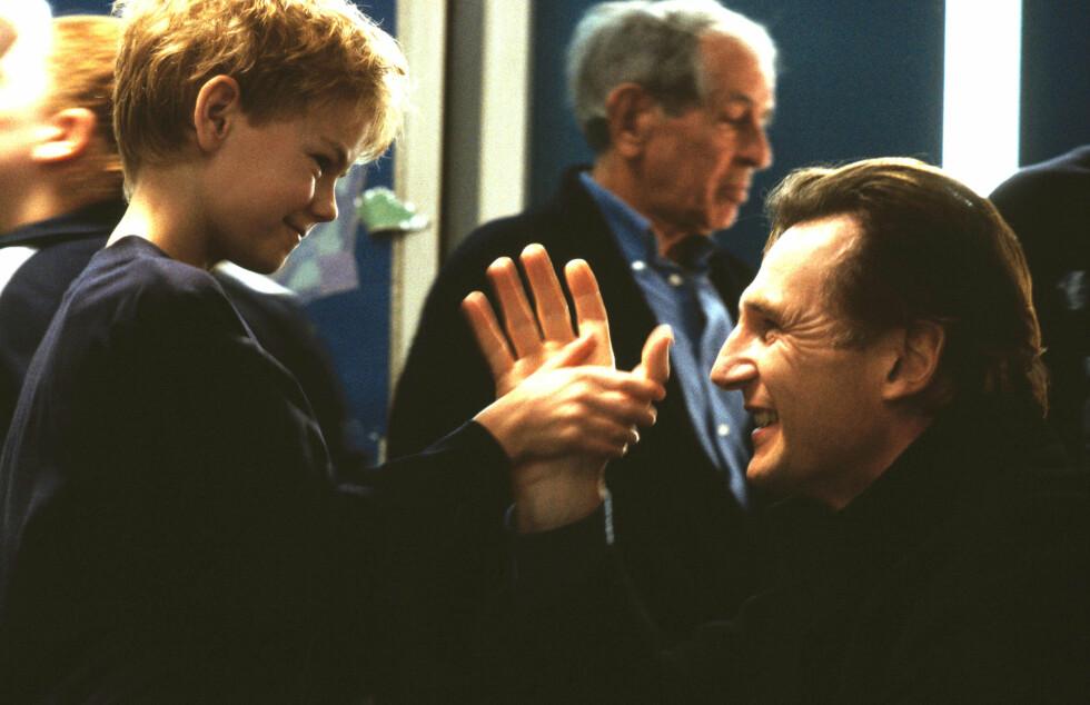 MISTET KONA: Thomas Brodie-Sangster og Liam Neeson i Love Actually. Neeson mistet i 2009 kona Natasha i en skiulykke mens Brodie-Sangster har blitt voksen og fått seg en rolle i Game of Thrones. Foto: All Over Press