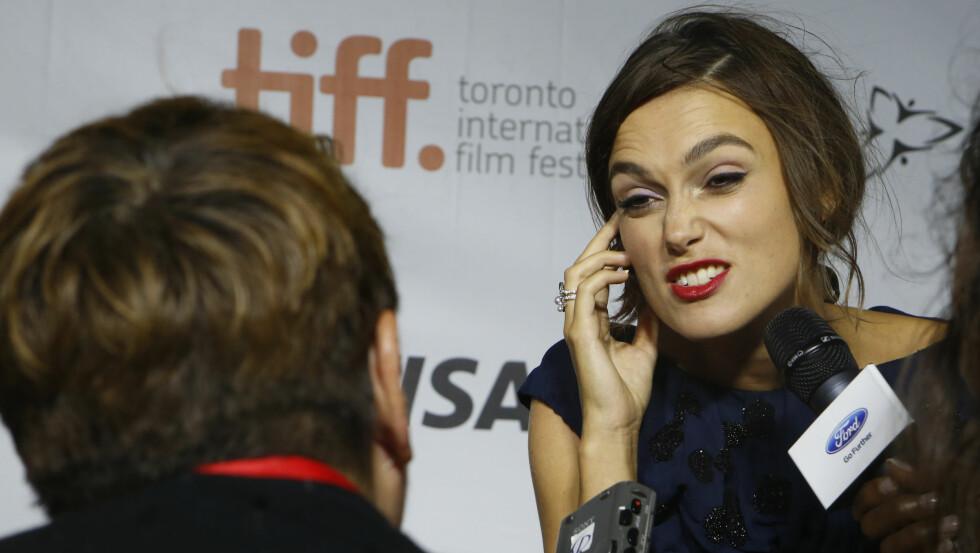 MÅTTE KONSENTRERE SEG: Hard vind og plaskende regn gjorde det vanskelig for Keira Knightley både å holde balansen og å gi intervjuer under Toronto International Film Festival i Canada. Foto: All Over Press