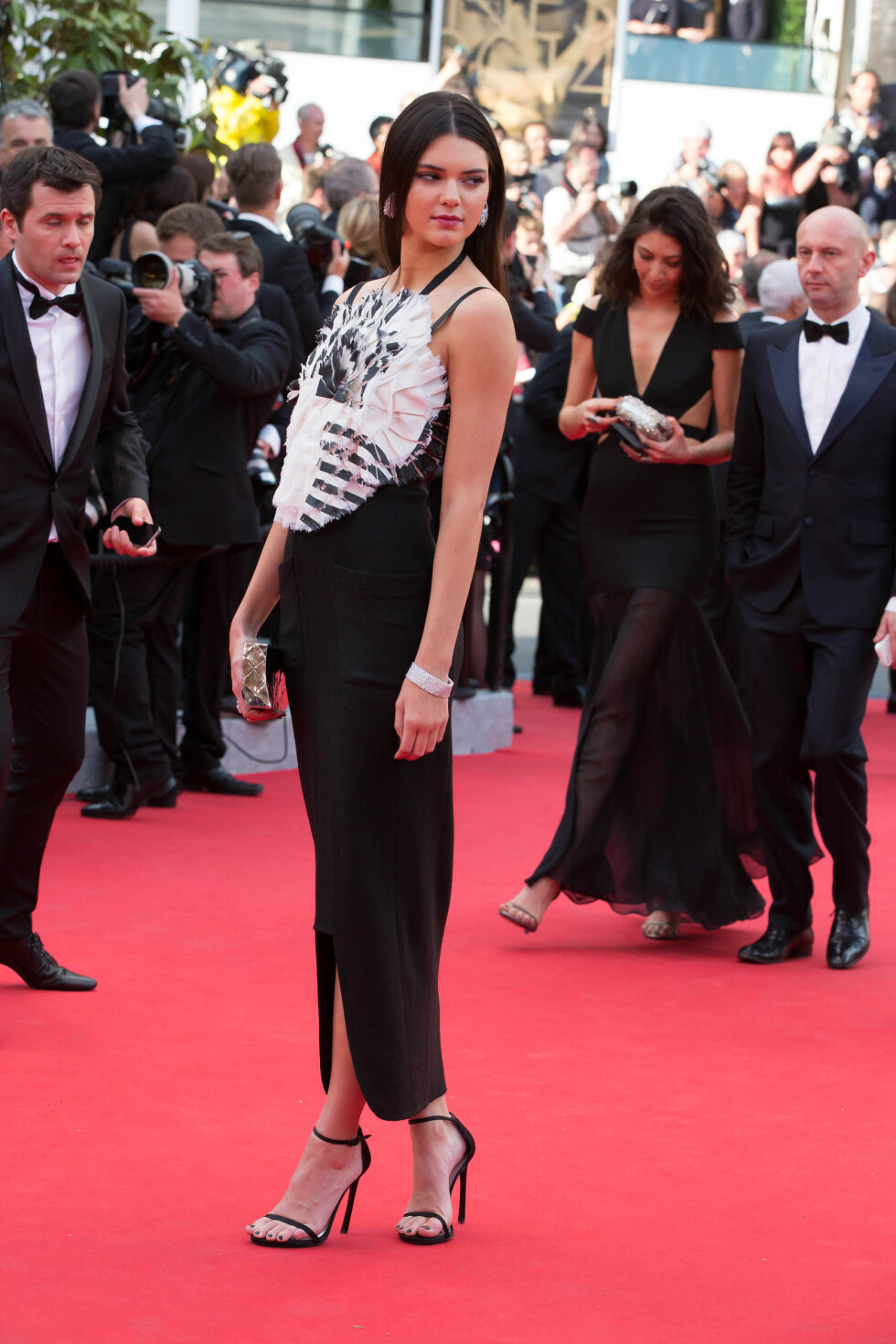 Kardashian-familiens nye motespire kom i en lang sort Chanel-kjole med hvite fjærdekorasjoner over brystet. Svarte stroppesandaler, en sølvfarget clutch og ringer fra Chopard var tilbehør.  Foto: Stella Pictures