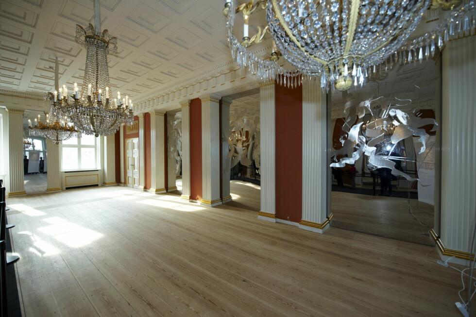 SPISESAL: Dette rommet er i dag møblert med et langbord med plass til 60 personer. Her har kunstneren Erik A. Fransen laget tre enorme nye speil i blankpolert stål med gravyr, som kan sees mellom de røde veggene på bildet. Foto: Stella Pictures