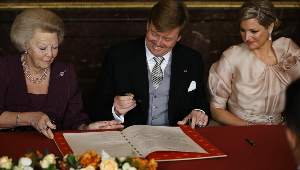 HER SKJER DET: Dronning Beatrix signerer protokollen som gir tronen til hennes sønn, Wilhem-Alexander.