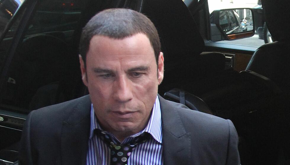 NOE MISTENKELIG: Det var noe litt unaturlig over håret til John Travolta i går. Foto: All Over Press