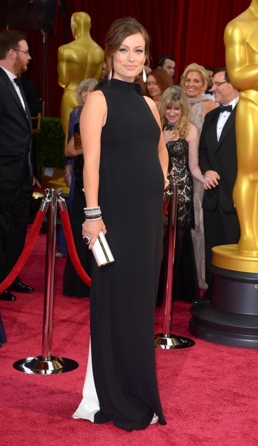 House-stjernen Olivia Wilde (29) viste frem sin voksende babymage i en svart kjole med hvite detaljer. Foto: REX/Stewart Cook/All Over Press