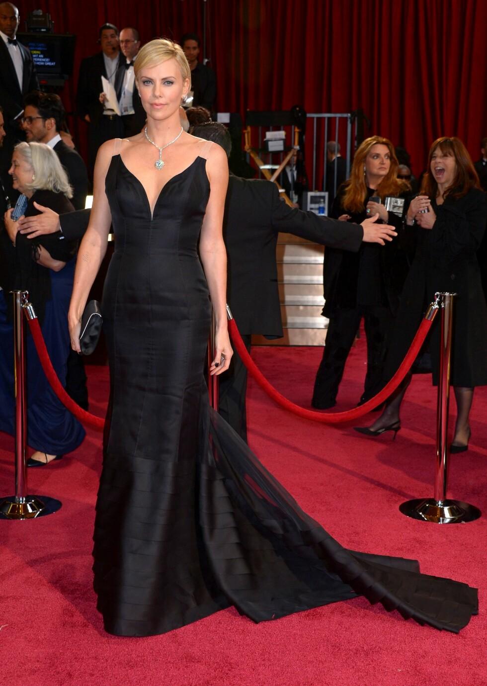 Charlize Theron (38) så nydelig ut i en svart figursydd kjole med slep. Foto: REX/Stewart Cook/All Over Press