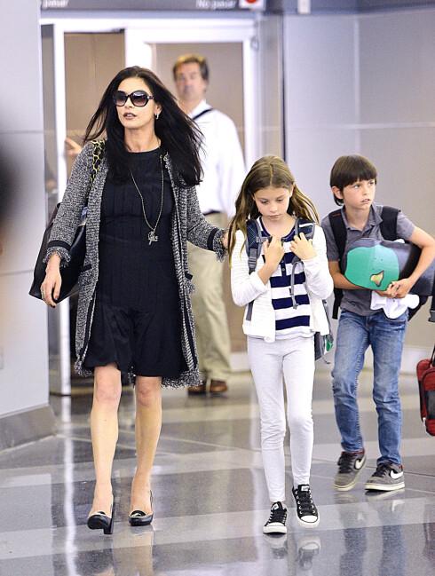 TØFT: Catherine Zeta-Jones med parets to barn Carys (10) og Dylan (13) på flyplassen i New York i sommer. Ifølge en kilde har Douglas uttrykt at de to barna har det bra til tross for at foreldrene har vært gjennom en tøff periode. Foto: Ahmad Elatab / Splash News/ All Over Press