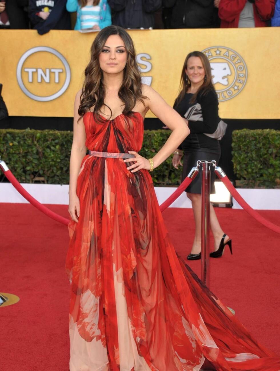 MILA KUNIS: Skuespillerinnen så nydelig ut i denne røde chiffonkjolen fra Alexander McQueen. Kunis bar også et lekkert armbånd fra Cartier.  Foto: All Over Press