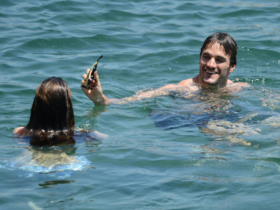 FLØRTET: Thom Evans ertet sin vakre kjæreste ved å ta solbrillene fra henne mens de svømmende svermet for hverandre i det varme vannet. Foto: All Over Press