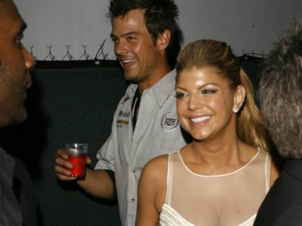 Musician Fergie, right, and boyfriend Josh Duhamel walk inside the Ocean Drive/Market America Super Bowl XLI party Saturday night, Feb. 3, 2007, in the South Beach section of Miami Beach, Fla.  (AP Photo/Chris Polk) Foto: AP
