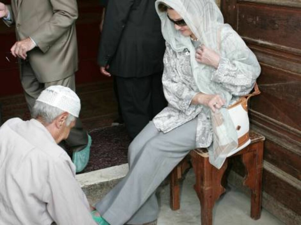 An Egyptian man removes plastic shoe covers from the feet of Queen Sonja of Norway after visting the Mohammed Ali Mosque in the ancient citadel of Cairo in Egypt, Thursday, Oct. 26, 2006. Queen Sonja is in Egypt for a five-day visit. (AP Photo/Cris Bouron Foto: AP/SCANPIX