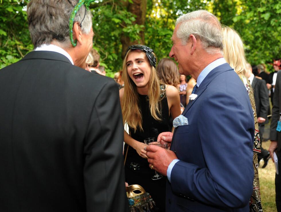 LØSSLUPPEN TONE: Tatoverings-praten ble svært munter, og både Cara (midten), Poppy og prins Charles lo godt.  Foto: All Over Press
